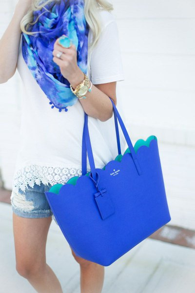 white crochet hem tee with denim shorts and royal blue purse