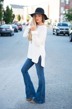 white long knit sweater with flared pull on jeans and floppy hat