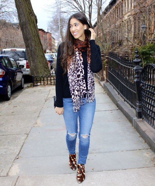 black sweater with leopard print scarf and light blue jeans