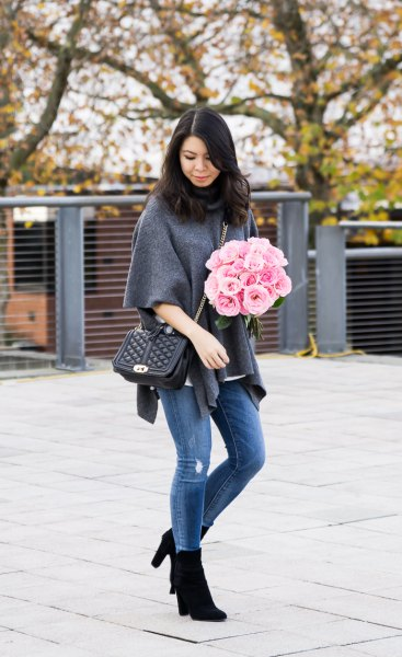 grey half sleeve poncho sweater with blue jeans and black boots