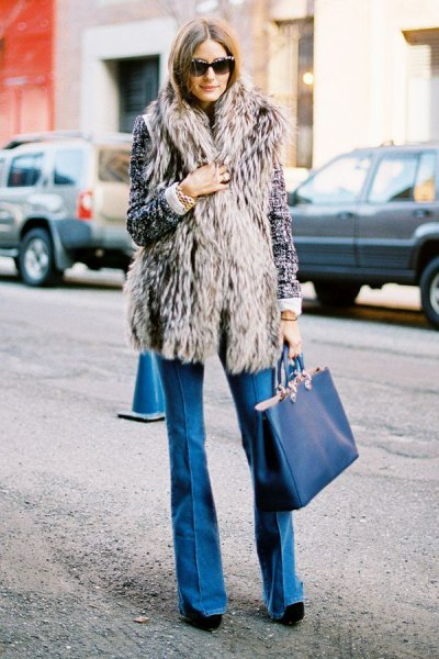 grey long vest with blue flared jeans and navy purse