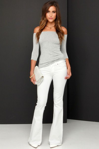 grey off the shoulder form fitting top with white flared jeans