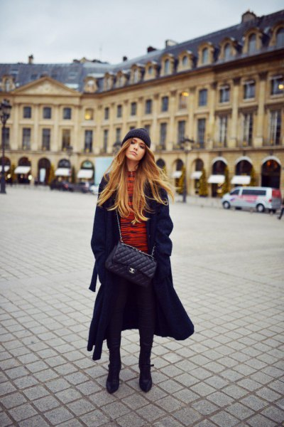 long black coat with orange sweater and knit hat