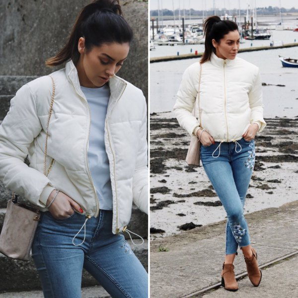 white down jacket with blue ripped cropped skinny jeans