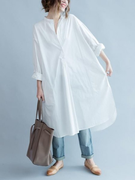 white long sleeve tunic shirt with blue cuffed jeans and loafers