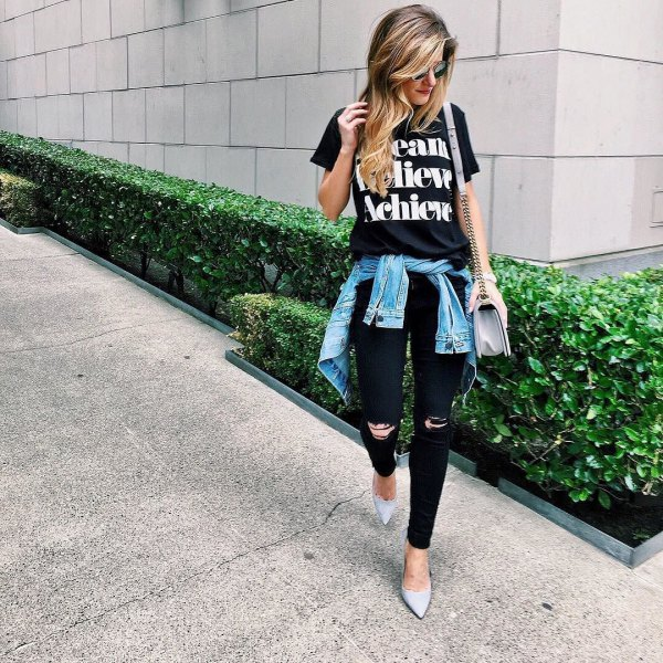black print tee with ripped jeans and denim jacket tied around waist