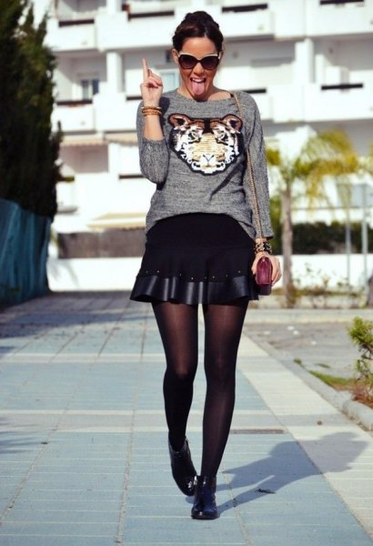 grey graphic sweater with black mini flared skirt and short boots