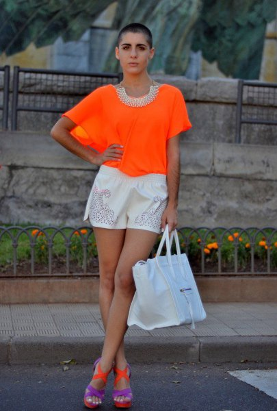 orange top with white mini shorts and blue sandals