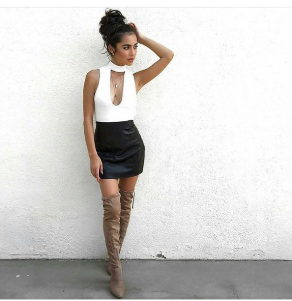 white choker neck low cut sleeveless top with black high rise mini skirt