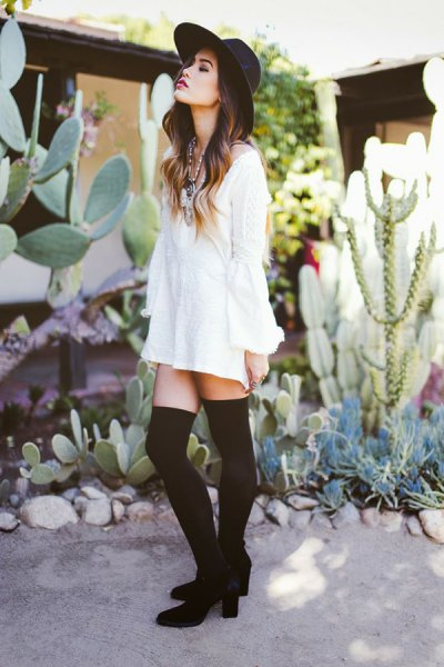 white long sleeve blouse dress with thigh high tights and heeled ankle boots