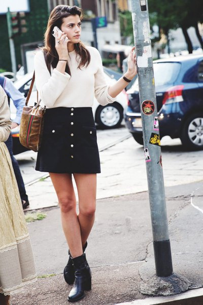 white ribbed sweater with black button front mini skirt and ankle boots