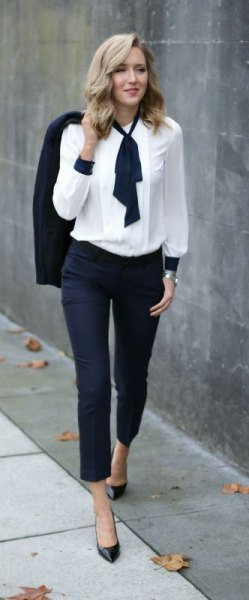 white with black tie neck detail and dark jeans