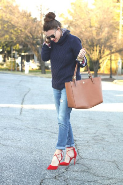 black cable knit sweater with blue cuffed jeans and red heels
