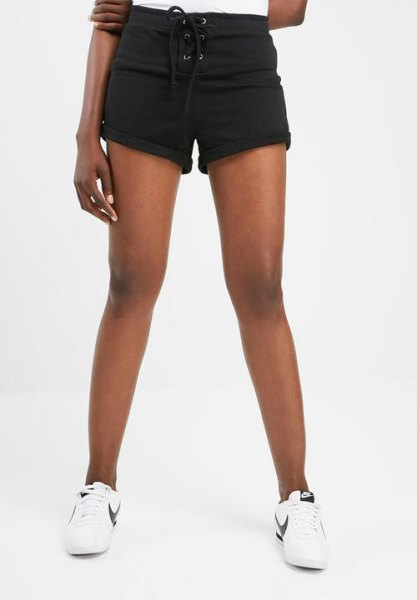 black cuffed mini sweat shorts with white t shirt and sneakers