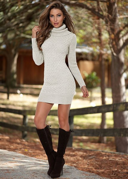 ivory turtleneck form fitting sweater dress with black knee high heeled boots