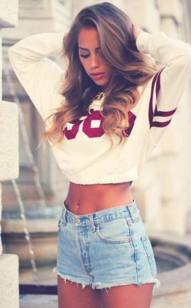 white and black cropped graphic sweatshirt with light blue denim shorts