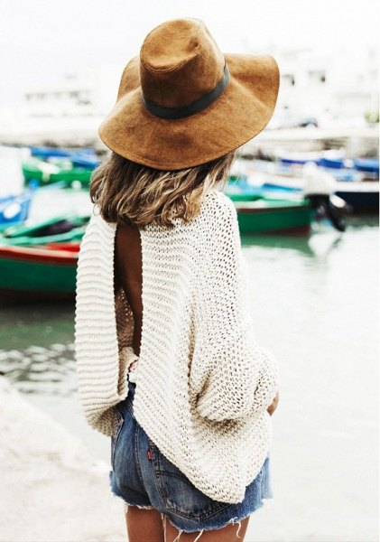 white long sleeve oversized sweater with blue denim shorts and floppy hat
