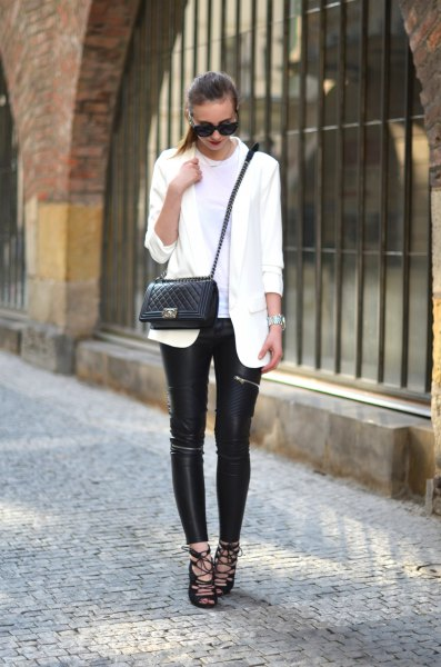 white oversized blazer with black leather leggings and lace up sandals