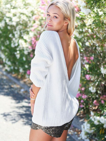 white oversized open back reverse deep v neck sweater with silver shorts