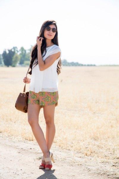 white sleeveless chiffon blouse with orange floral printed mini summer shorts