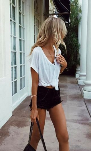 white v neck knotted t shirt with ripped black denim shorts