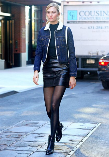 blue denim jacket with navy crew neck sweater and black leather skirt