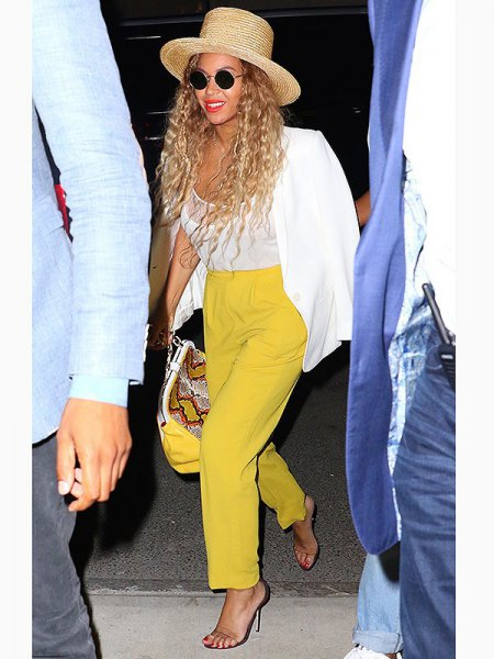 white blazer with mustard yellow straight leg pants and straw hat