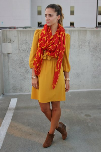 yellow fit and flare mini dress with orange and gold scarf