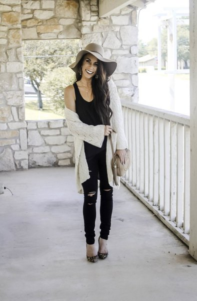 black scoop neck tank top with white cable knit long cardigan and floppy hat