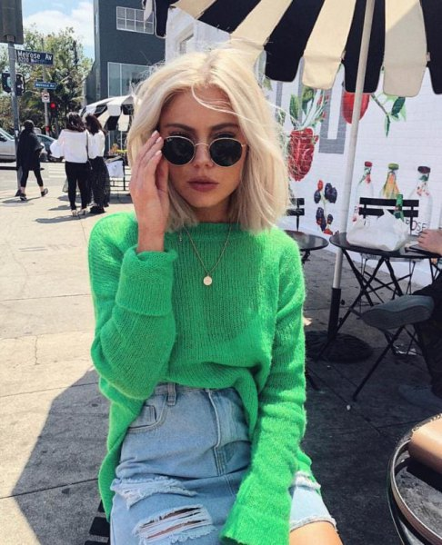 green ribbed sweater with blue high rise ripped mini skirt