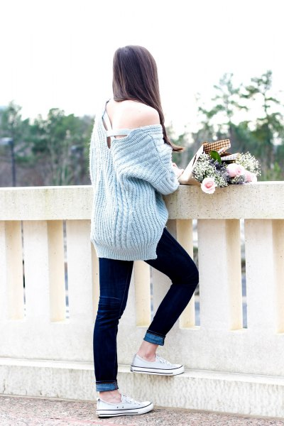 grey one shoulder ribbed chunky sweater with dark blue cuffed skinny jeans