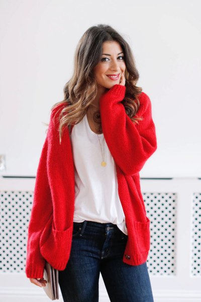 red chunky cardigan sweater with white scoop neck tee and dark blue skinny jeans
