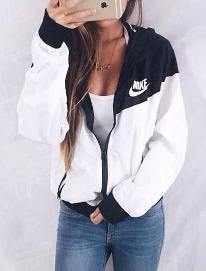 white and black nike windbreaker with low neck tank top and jeans