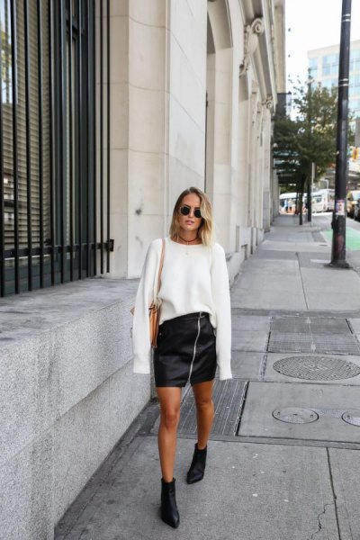 white oversized knit sweater with black mini leather zipper skirt