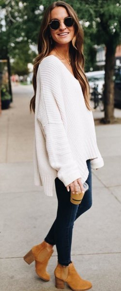 white v neck chunky sweater with dark blue skinny jeans and camel boots