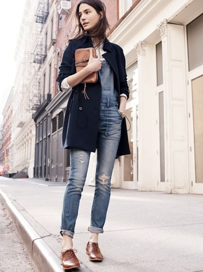 black long wool coat with greyish blue cuffed ripped jeans and brown shoes