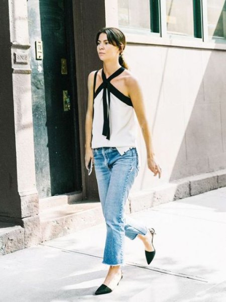 white and black halter top with flared jeans and kitten heel pumps