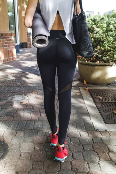 white cutout back tee with black sports leggings and pink sneakers