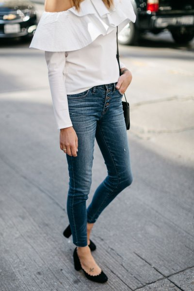 white one shoulder ruffle shoulder blouse with button fly jeans