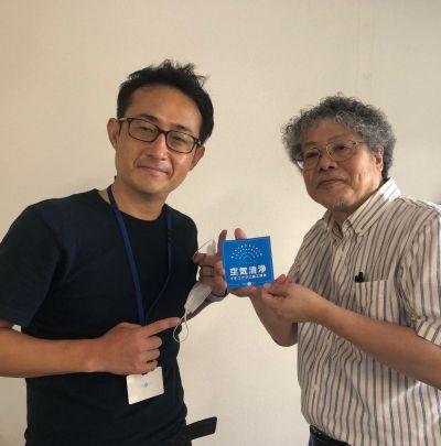 ロイヤル住建の岡田正幸社長から施工処理ステッカーを受け取るFMおおつの古田誠