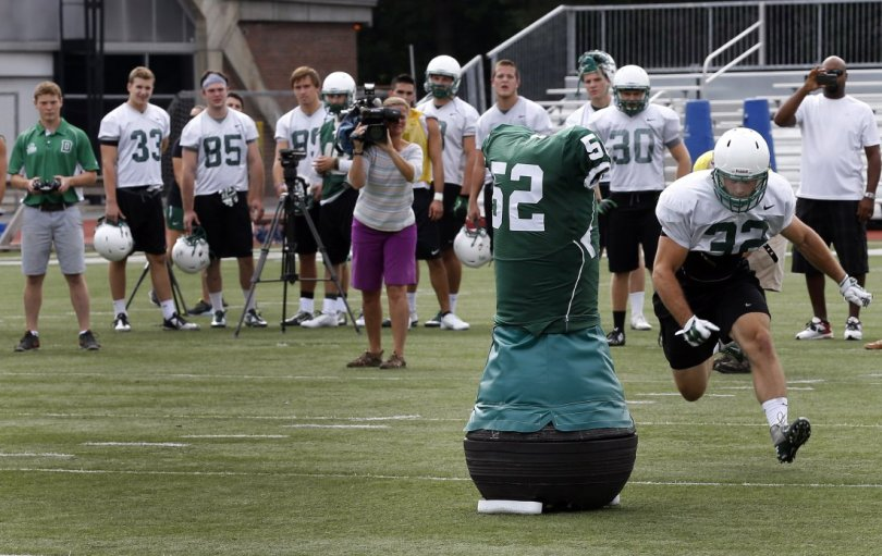 """Dartmouth College Engineering graduate Quinn Connell, upper left, controls the movement of the team's """"Mobile Virtual Player"""" during college football practice Wednesday Aug. 26, 2015, in Hanover, N.H.  In an effort to avoid concussions, the team practices with its new """"Mobile Virtual Player,"""" which the school says is the only powered device that simulates a real football player in size, weight, agility and speed. (AP Photo/Jim Cole)"""