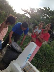 Nido with his wife Liza and two children showing the tap stand project of Kalahi-CIDSS