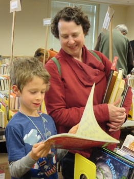 Board member Shannon Turlington browses the book sale with her son Sean.