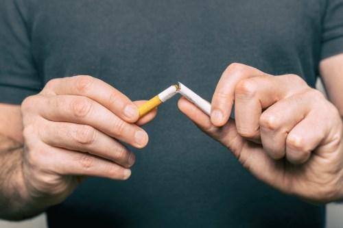 Quitting smoking - male hand crushing cigarette