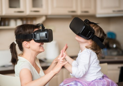 Mother and child playing together with virtual reality headsets indoors at home