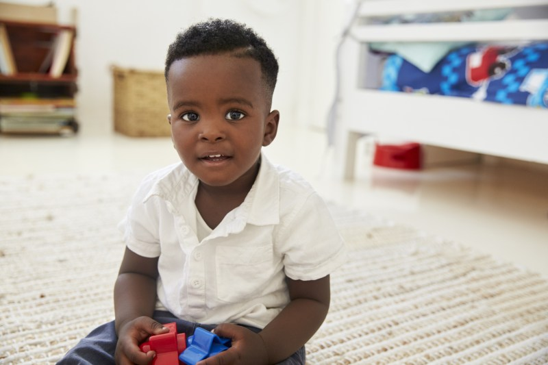Portrait Of Happy Boy Playing With Toys In Playroom