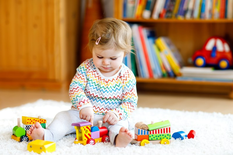 Adorable cute beautiful little baby girl playing with educational wooden toys at home or nursery. Toddler with colorful train. Happy healthy child having fun with different toys. Kid learning skills