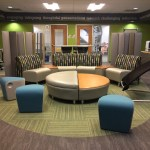 Photograph of the Focused Inquiry Learning Lounge, a room on the 5th floor of Harris Hall with work space for students. The room has a variety of chairs, tables, and private work spaces pictured.