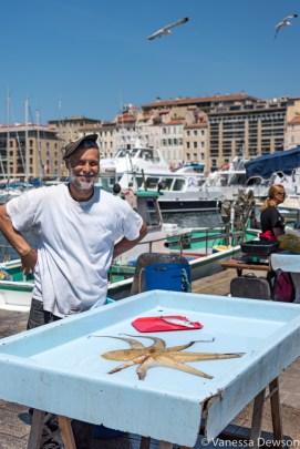 A vendor at the Marseille Fish Market. Photo by: Vanessa Dewson