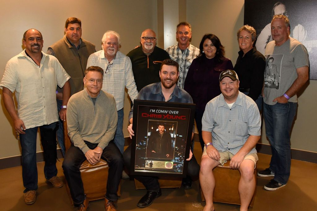 "Sony Music Nashville presented Chris Young with a plaque celebrating the recent RIAA Gold certification of his current single, ""I'm Comin' Over."" Back Row (L-R): Paul Barnabee (SVP, Marketing, Sony Music Nashville), Jim Catino (VP, A&R, Sony Music Nashville), Bill Simmons (Fitzgerald Hartley), Larry Fitzgerald (Fitzgerald Hartley), Steve Hodges (EVP, Promotions & Artist Development, Sony Music Nashville), Caryl Healey (VP, Sales, Sony Music Nashville), Angie Magill (VP, Legal & Business Affairs, Sony Music Nashville), Keith Gale (SVP/National Promotion, RCA) Front Row (L-R): Randy Goodman (Chairman & CEO, Sony Music Nashville), Young, Josh Easler (Director/National Promotion, RCA) Photo credit: Rick Diamond/Getty Images for Sony Music Nashville"